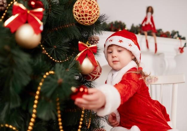 Little boy dressed as santa decorating the christmas tree
