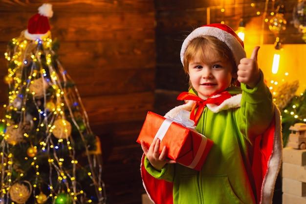 屋内でプレゼントを持っているサンタに身を包んだ小さな男の子