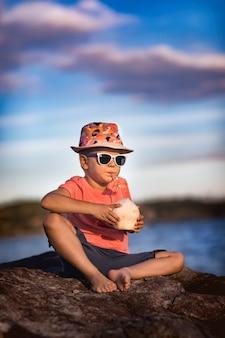 Маленький мальчик пьет кокос, сидя на скале у моря