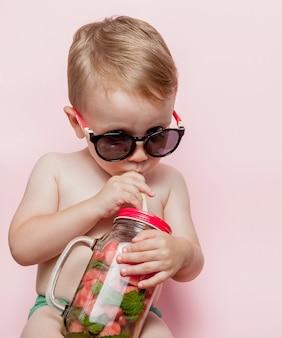 ピンクの背景にスイカと氷のかけらで新鮮なレモネードを飲む少年。