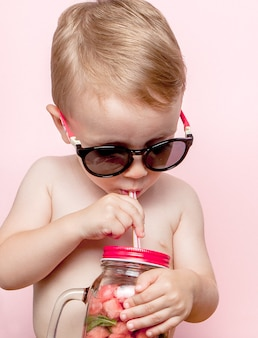 Little boy drinking fresh lemonade with piece of watermelon and ice on pink.