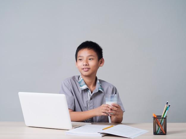 Маленький мальчик пьет молоко во время учебы онлайн дома