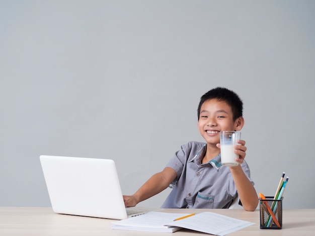 Little boy drinking milk while studying online at home