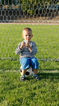 Little boy drinking refreshing fruit juice while taking a break sitting on the ball in the goals while playing soccer