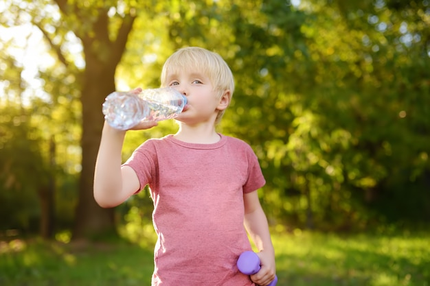 Little boy drinking water during workout with dumbbells