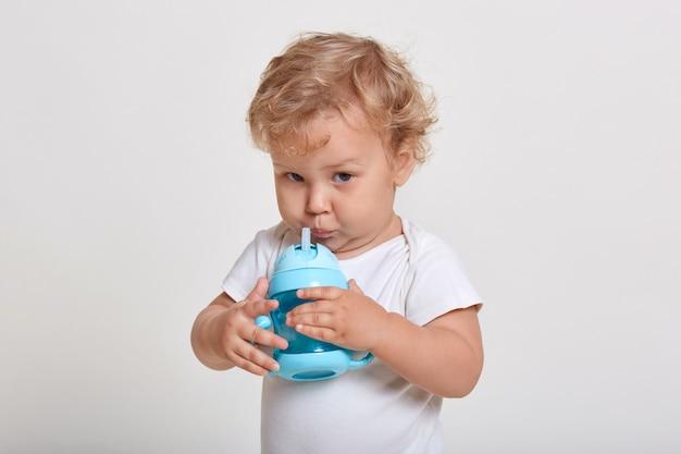 Маленький мальчик пьет воду из бутылки, одетый в футболку, смотрит прямо в камеру
