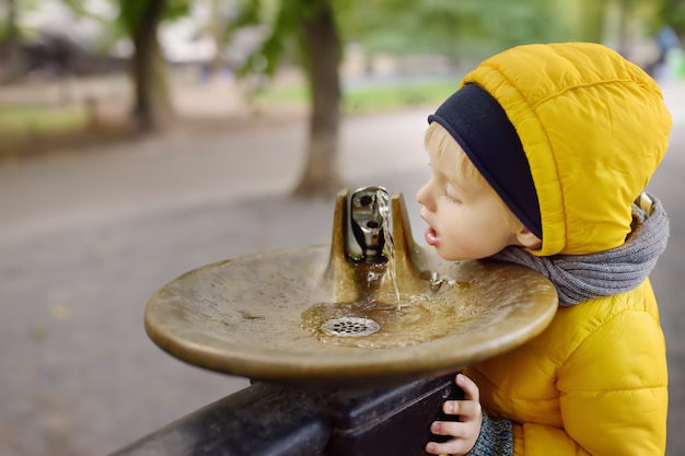 Little boy drinking water from city fountain during walking in central park