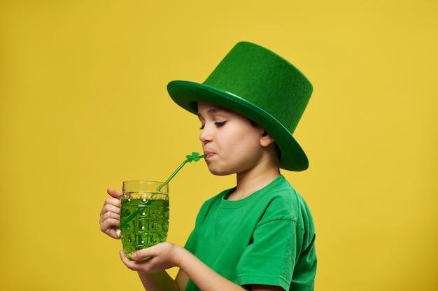 어린 소년은 클로버 잎 장식으로 빨대에서 마신다. 성 패트릭의 날을 축하하는 녹색 음료