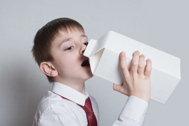 Little boy drinks from a large white package. white shirt and red tie. light background