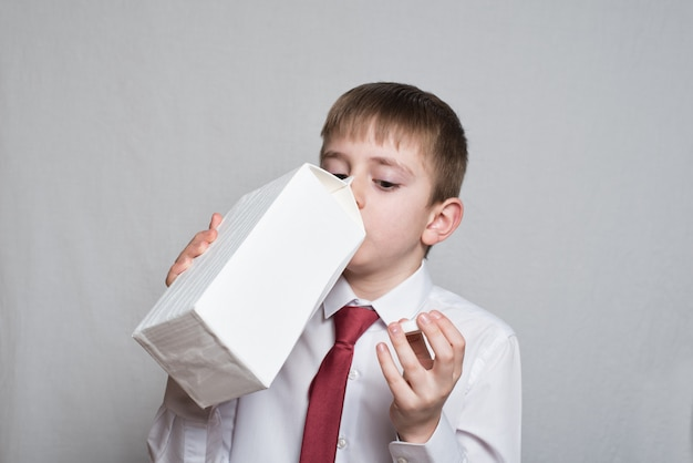 Little boy drinks from a large white package. white shirt and red tie.
