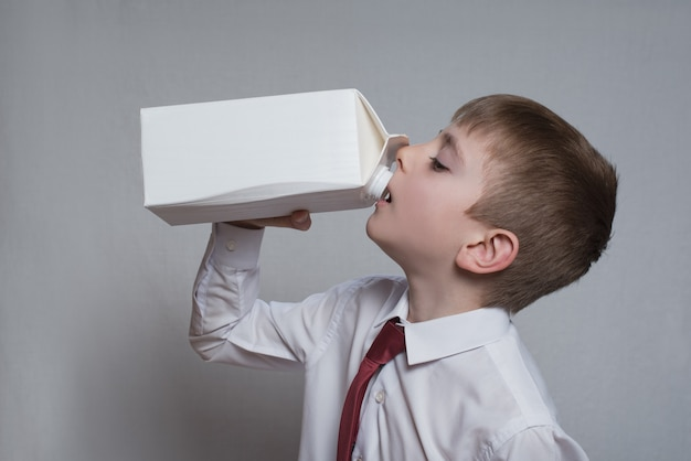 Little boy drinks from a large white package.