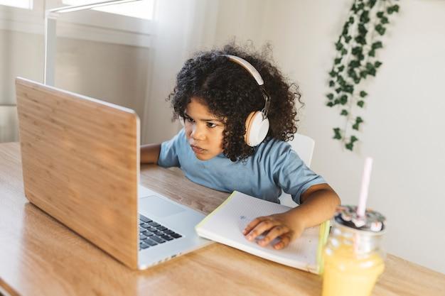 어린 소년은 컴퓨터를 하면서 주스를 마신다