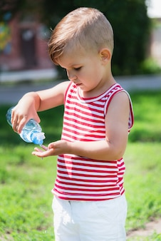 Маленький мальчик пьет воду из бутылки в жаркий день, играя на лугу