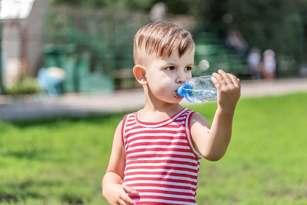 Little boy drinks water from a bottle on a hot day playing on the meadow