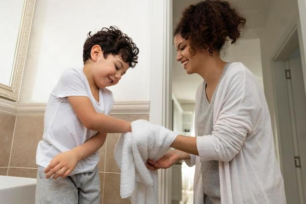 그의 엄마와 함께 손을 건조하는 어린 소년