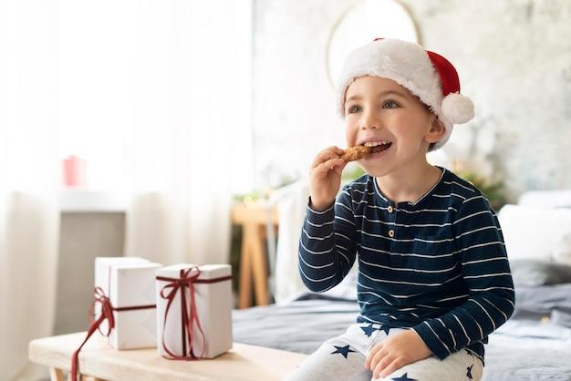 Маленький мальчик ест рождественское печенье