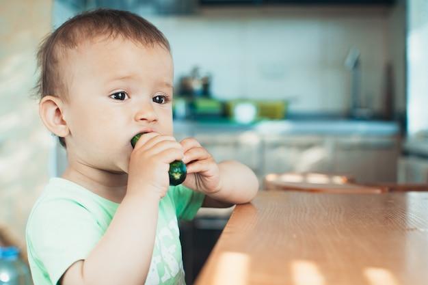 Маленький мальчик ест свежий огурец на кухне при дневном свете