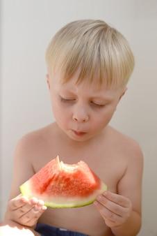Маленький мальчик ест сочный арбуз