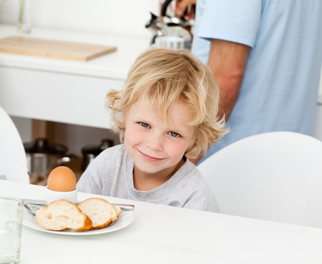 Little boy eating boiled egg and bread at breakfast