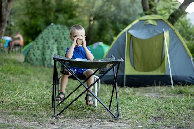 백그라운드에서 텐트와 자연 햇빛에 캠핑 사이트에서 야외 아침을 먹는 어린 소년.
