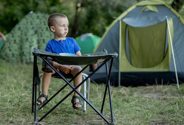 캠핑 사이트에서 야외 아침을 먹고 어린 소년
