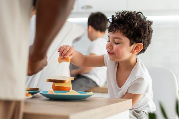彼のお父さんと一緒に朝食を食べる小さな男の子