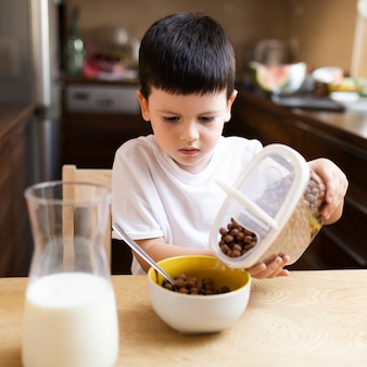 Little boy eating cereals with milk