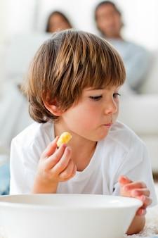 Маленький мальчик ест чипсы, лежащие на полу