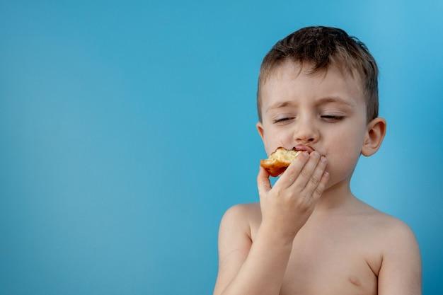 青の背景にドーナツチョコレートを食べる少年。かわいい幸せな少年が彼の口の周りにチョコレートを塗った。子供のコンセプト、子供のためのおいしい食べ物