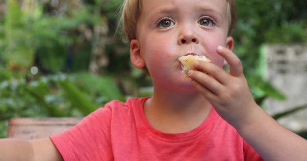 Little boy eating fried chicken garden on background