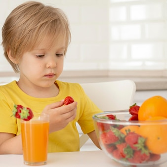 Little boy eating fruits