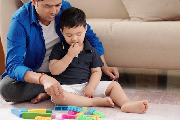 어린 소년은 포도를 먹고 집에서 바닥에 앉아 있을 때 플라스틱 블록에서 타워를 만들 것을 제안하는 아버지의 말을 듣고 있습니다.