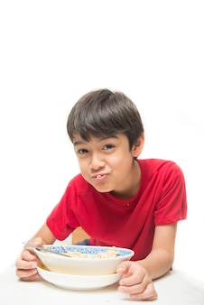 Little boy eating instant noodle on white