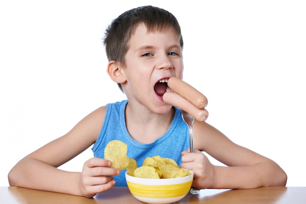 Little boy eating sausages and potato chips isolated