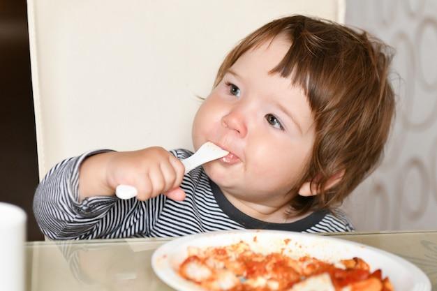 小さな男の子がカフェでフォークから食べ物を食べる