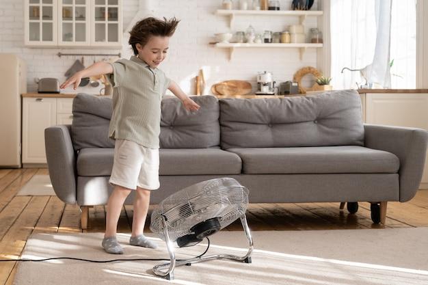 Маленький мальчик наслаждается воздушным потоком от вентилятора в гостиной, милый маленький ребенок играет с вентилятором, дующим ветром