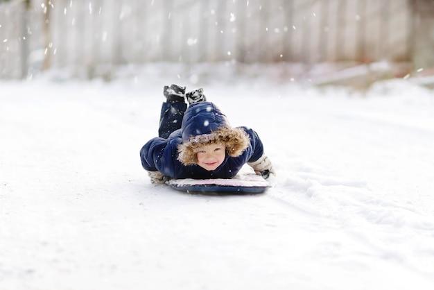 Маленький мальчик, наслаждаясь катанием на санях в снегу