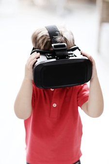 Little boy entertaining with virtual reality