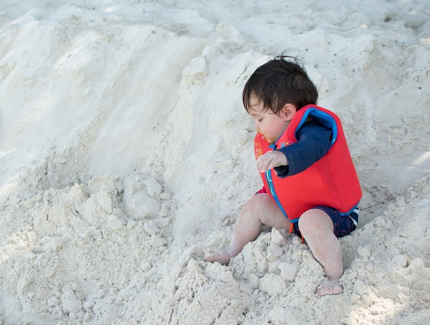 Little boy fall down from the sand at the beach