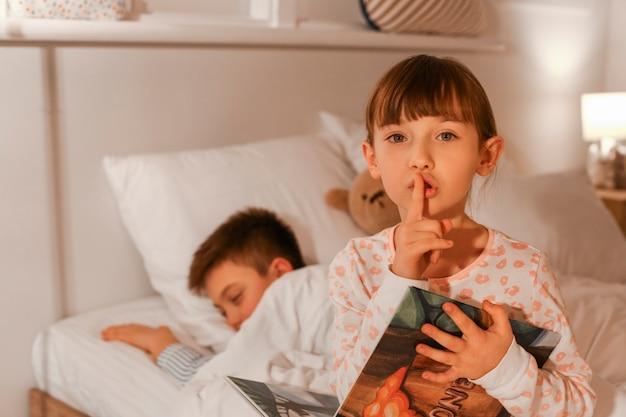 Маленький мальчик засыпает, пока его сестра читает сказку на ночь дома