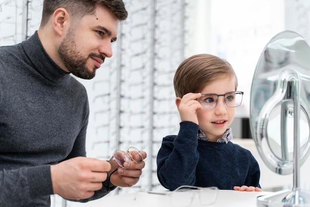 Ragazzino e padre in negozio cercando su occhiali