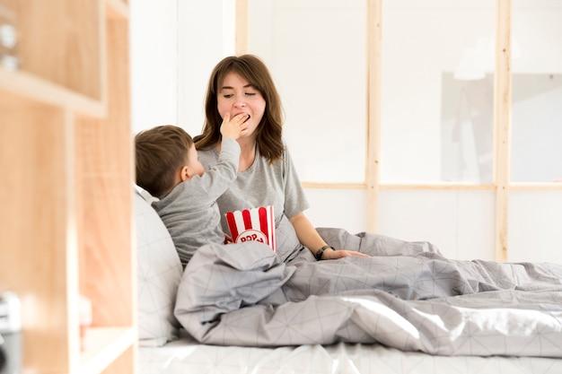 Little boy feeding his mom pocorn