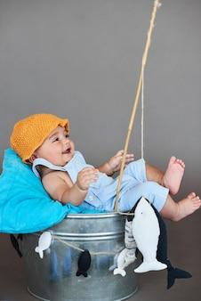 Маленький мальчик, рыбалка на сером фоне