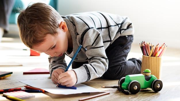 Маленький мальчик сосредоточен на выполнении своей домашней работы