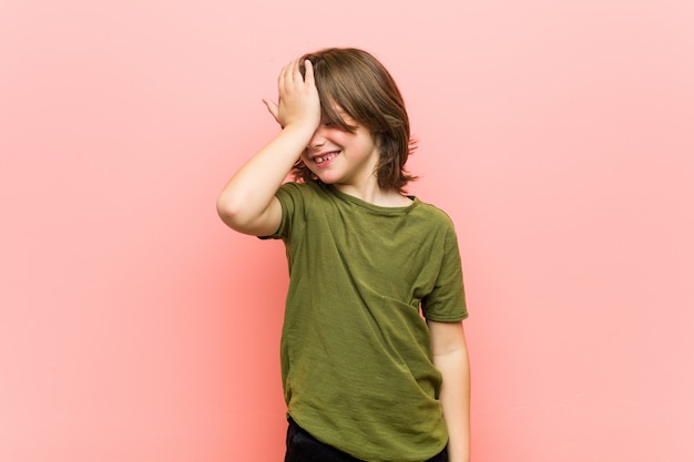 Little boy forgetting something, slapping forehead with palm and closing eyes.