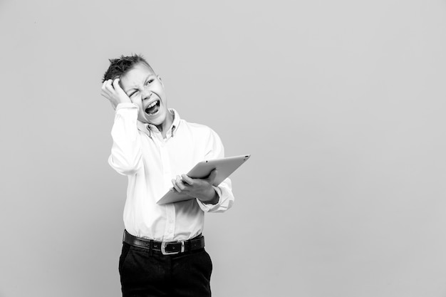 Little boy in formal clothing looking terrified while holding tablet and posing on gray surface.