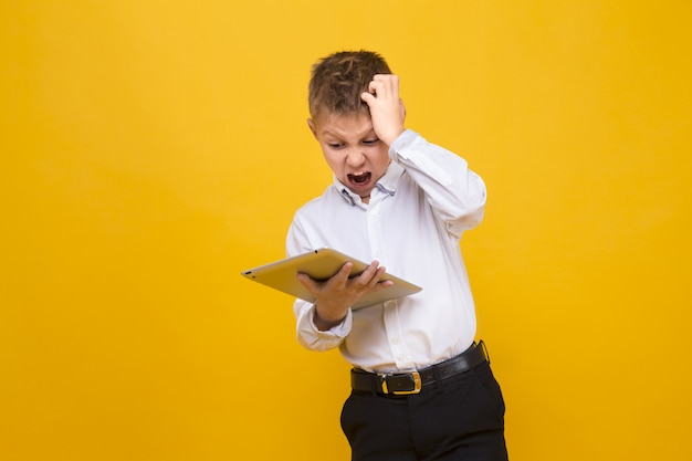 Little boy in formal clothing looking terrified while holding tablet and posing