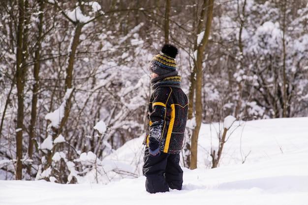 Маленький мальчик из заднего пребывания в снежном лесу