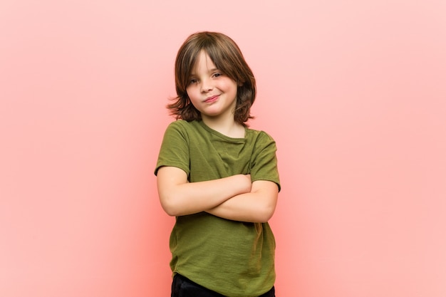 Little boy frowning face in displeasure, keeps arms folded