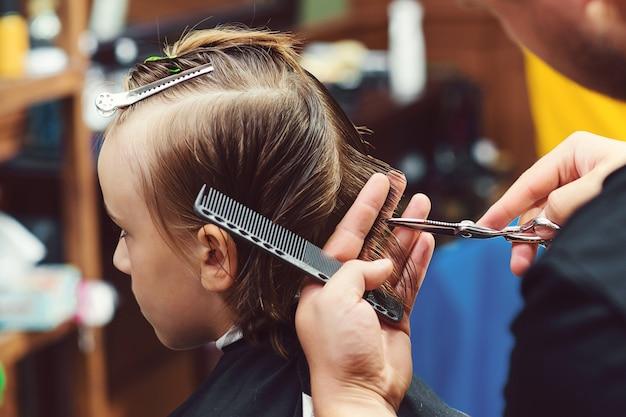 美容師によって散髪されている小さな男の子